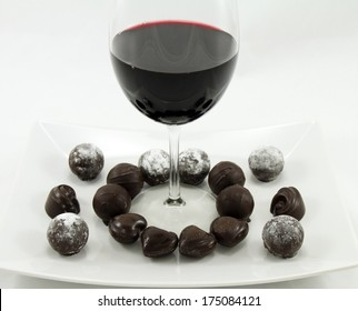 A glass of wine and assorted chocolates on a white plate.