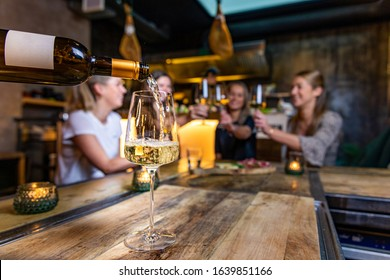 Glass of wine being poured while girls clinking their glasses in the background