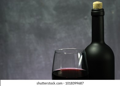Glass of wine A black bottle of red wine on a dark background.