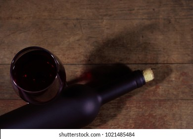 Glass of wine A black bottle of red wine on a wooden table. Beautiful dark background