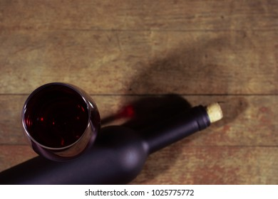 Glass of wine A black bottle of red wine on a wooden table.