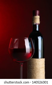 Glass of wine with bottle on bright red background