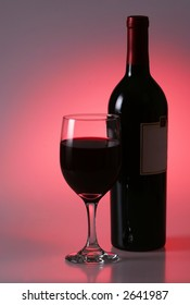 a glass of wine and wine bottle on red