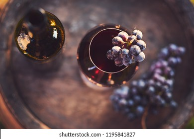 A glass of wine and a bottle of red wine on a wooden barrel, top view