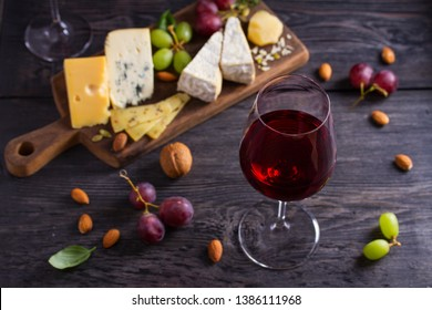 Glass of wine with cheese, grapes, and nuts on black wooden table. Wine and food. View from above, top studio shot