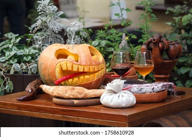 A glass of wine with decorations for Halloween on the table. Autumn still life card with pumpkin. Halloween pumpkin and wine glass. Dinner for Halloween.