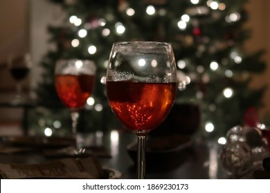 Glass of rosé wine in the foreground. Blurred Christmas tree lights and another glass in the background.