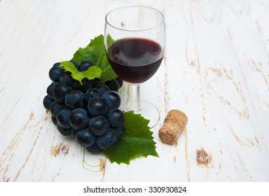Glass of wine with grapes on a wooden table