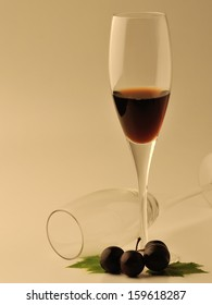 Glass of wine and grapes over white background