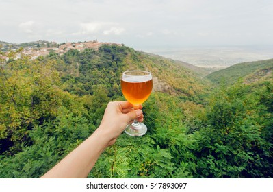 Glass of wine in hand of tourist in a natural landscape of green Alazani Valley, Georgia. Homemade beverage