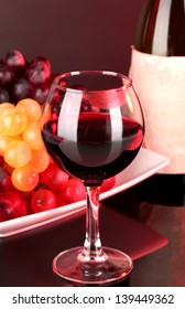 Glass of wine with lipstick imprint, grapes and bottle on dark background