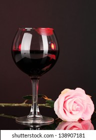 Glass of wine with lipstick imprint on dark background