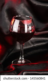Glass of wine with lipstick imprint on black satin background