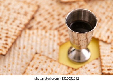 Glass of wine and matzah on background.