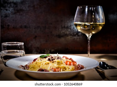 Glass with wine near appetizing spaghetti pasta with shrimps, grated cheese, jamon, tomato sauce and basil in white plate on decorated table with light tablecloth