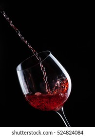 a glass of wine on a black background