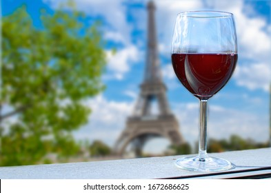 Glass of wine on Eiffel tower blur background. Sunny view of glass of red wine overlooking the Eiffel Tower in Paris, France