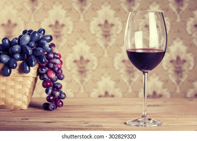 Glass of wine on wooden table against of vintage wallpaper background