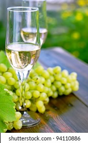 glass of wine on a wooden table. Bunches of grapes.