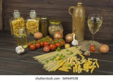 Glass of wine and pasta. Preparing homemade pasta. Pasta and vegetables on a wooden table. Dietary food. Pasta, tomatoes, onion, olive oil and basil on wooden background.
