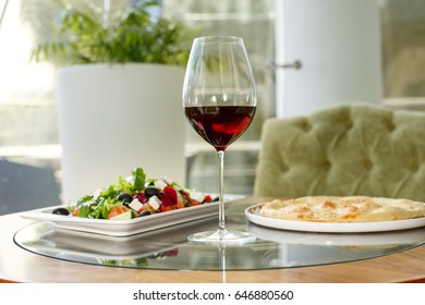 glass of wine and a salad on the table in a restaurant