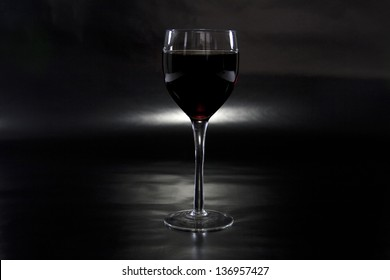 Glass of wine spotlighted on reflective black background