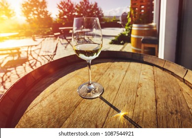 A glass of wine stands on a wine barrel against the background of the morning landscape