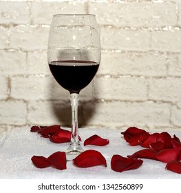 A glass of wine with traces of lipstick is surrounded by red rose petals against a brick wall.