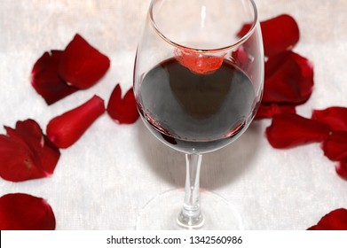 A glass of wine with traces of lipstick is surrounded by red rose petals.