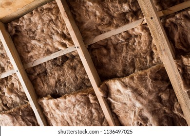 Glass wool in a wooden frame on a inclined wall near the wooden ceiling in a private house. Warming the house with fiberglass.