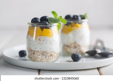Glass of yogurt with blueberries and mango mousse, chia seed and oat granola