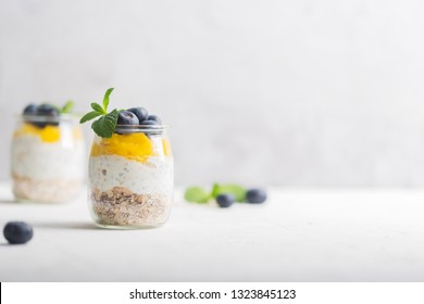 Glass of yogurt with blueberries and mango mousse, chia seed and oat granola, copy space