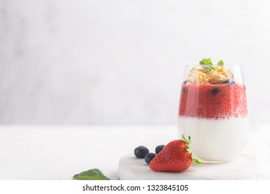 Glass of yogurt or panna cotta with strawberry mousse and granola on a white background