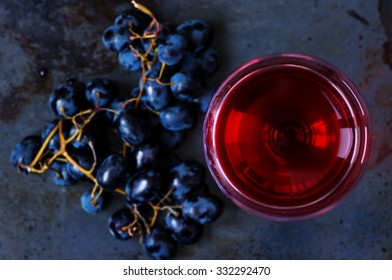 Glass of young red wine with grapes on top