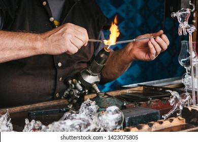 A glassblower makes a glass product. Handwork. Profession or occupation or hobby.