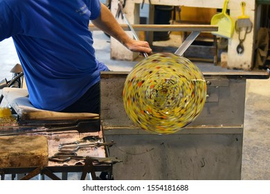 A glassblower makes a vase of glass in a manufactory on the island of Murano, Venice, Italy.