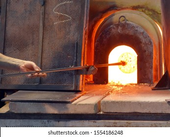 A glassblower makes a vase of glass in a manufactory on the island of Murano, Venice, Italy. Crucible furnace.