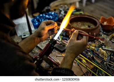 a glassblower man made Handicraft from melted glass in glassblowing workshop. Glass art is shaping at the end of glassblowing pipe.