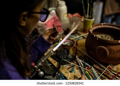 a glassblower women made Handicraft from melted glass in glassblowing workshop. Glass art is shaping at the end of glassblowing pipe.