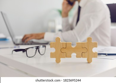 Glasses and 3 joined jigsaw puzzle pieces placed on office desk, blurred employee working on laptop computer in background. Concept of effective management, business solutions and finding missing link