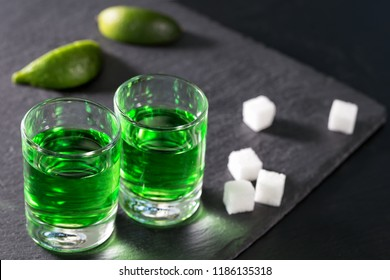 Glasses of absinthe with lime and sugar on a black background