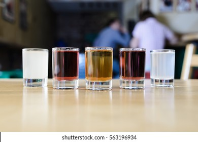 Glasses with alcohol of different colors on a wooden table