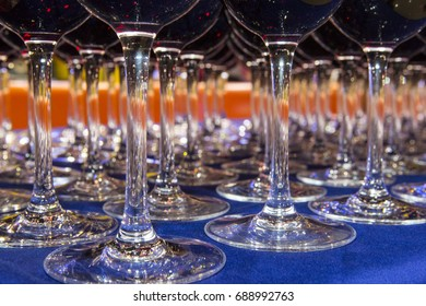A lot of glasses with alcohol, white wine glasses crossing red wine glass. Wine bottle pouring row of glasses for tasting, service in night party event. wineglass with wine close-up before cafe party