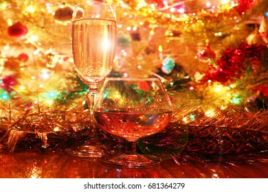 Glasses with alcoholic drinks on the background of a Christmas tree