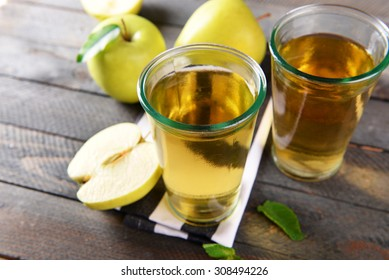 Glasses of apple juice on wooden background