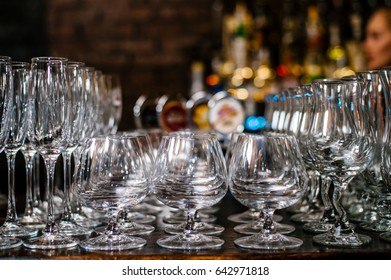 Glasses in the bar. Beautifully stand on the bar. Clean glasses. Blurred background.