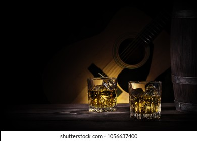 Glasses and a barrel of whiskey on a background of a guitar