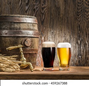 Glasses of  beer and ale barrel on the wooden table. Craft brewery.