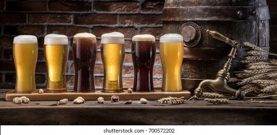 Glasses of beer and ale barrel on the wooden table. Craft brewery. Six varieties of beer.