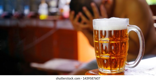 glasses  of Beer and background images are male headaches. The result of excessive alcohol consumption.